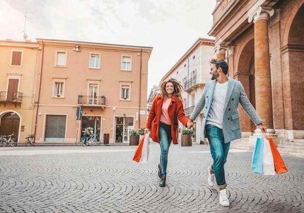 Beau couple d'amoureux portant des sacs à provisions en cours d'exécution dans la rue de la ville et profitant ensemble de vacances.