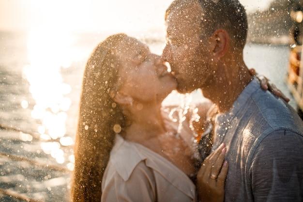 Beau couple amoureux s'embrasse et s'embrasse sous les jets d'eau dans un hôtel spa de luxe en lune de miel, vacances sous les tropiques. mise au point sélective