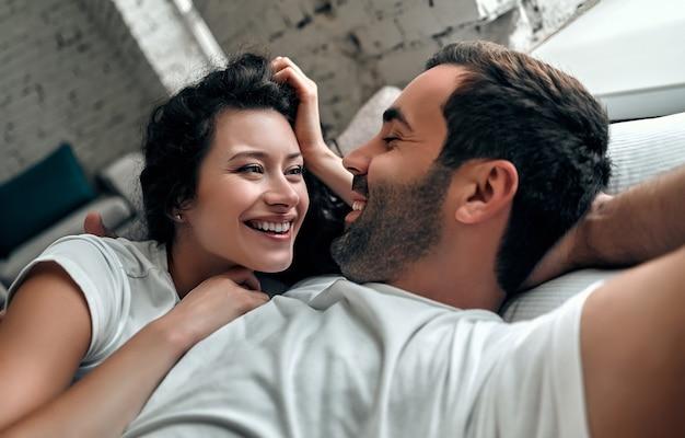 Beau couple d'amoureux s'embrasser au lit