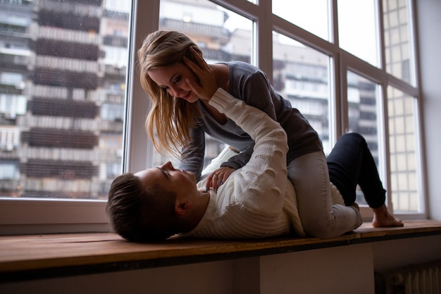 Beau couple d'amoureux s'enlaçant et s'amuse dans leur chambre près de la fenêtre