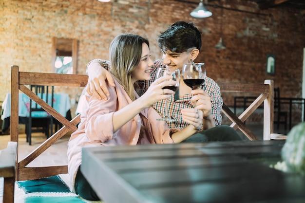 Beau couple amoureux se regardant et grillage avec des verres à vin.