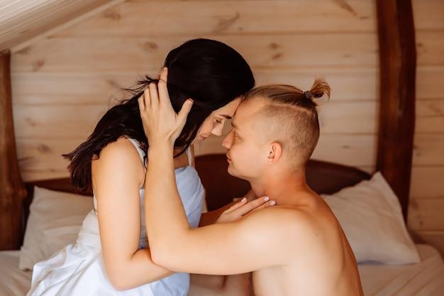 Un beau couple d'amoureux se regarde dans les yeux au lit