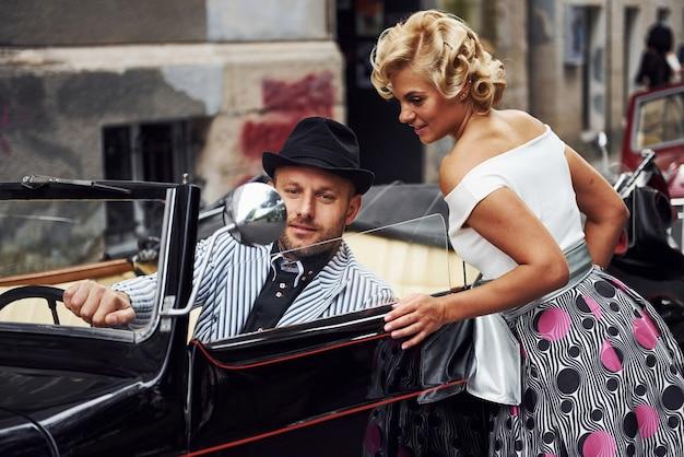 Beau couple à l'ancienne est en ville avec une voiture rétro.