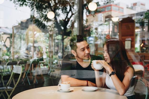 Beau couple asiatique prenant un café