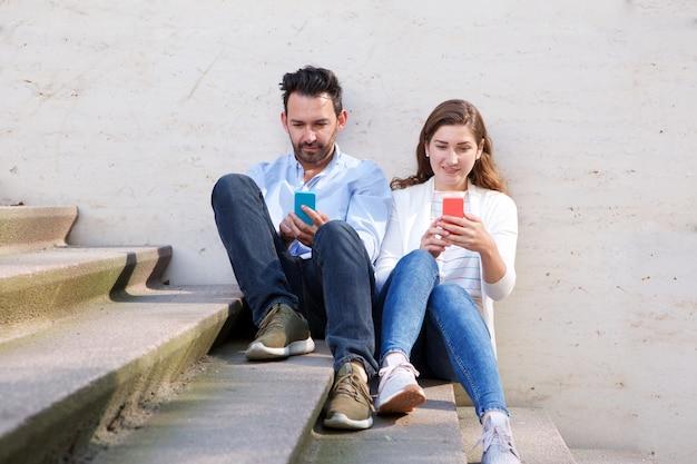 Beau couple assis ensemble dans l'escalier avec les téléphones mobiles