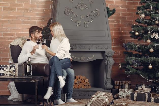 Beau couple assis à la maison près de l'arbre de noël
