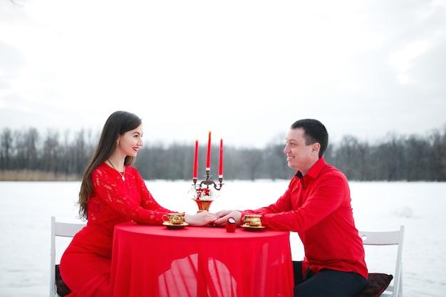 Beau couple assis à une table avec un chandelier sur fond de neige en vêtements rouges