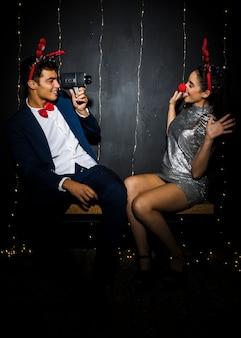Beau couple avec bandeaux en bois de cerf et nez rigolo capturant en vidéo