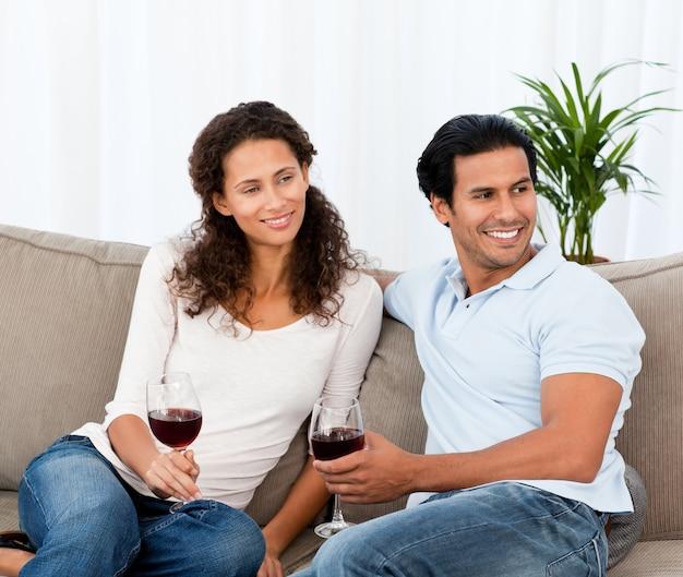 Beau couple, boire du vin rouge assis sur le canapé