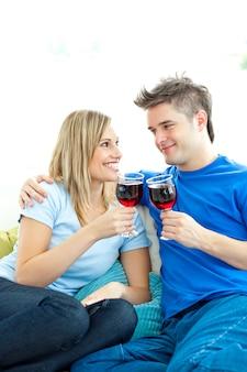 Beau couple boit du vin ensemble dans le salon