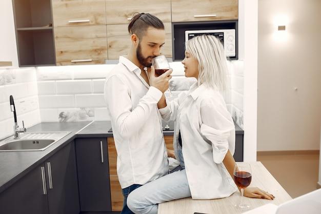 Beau couple boit du vin rouge dans la cuisine