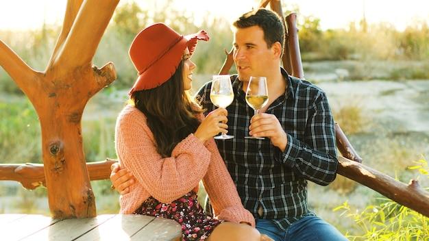 Beau couple caucasien dans les fusées éclairantes du soleil tinter des verres avec du vin blanc.
