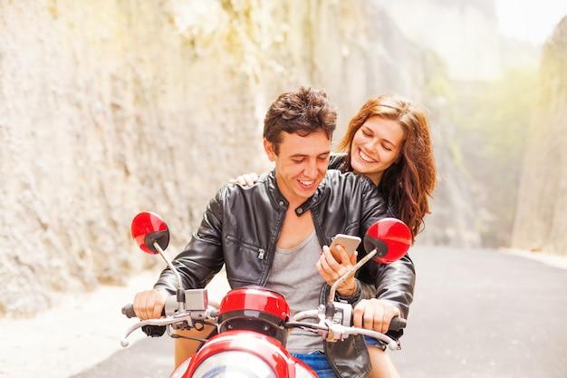 Beau couple caucasien sur un vélo à l'aide d'un smartphone
