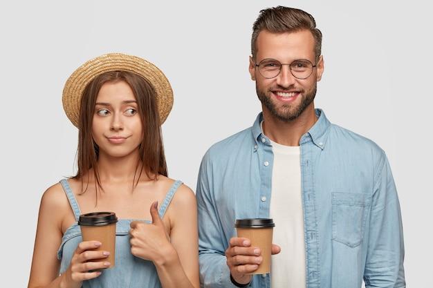 Beau couple charmant posant contre le mur blanc