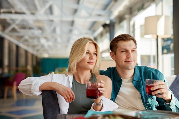 Beau couple charmant s'asseoir à parler avec des amis