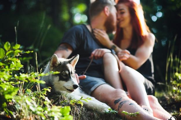 Un beau couple et un chien se reposent dans la forêt