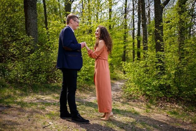 Beau couple dans les bois. une fille avec une coupe de cheveux élégante embrasse son homme en costume. l'extérieur rustique détaille le portrait photographique. femme heureuse et petit ami