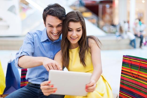 Beau couple dans un centre commercial à la recherche sur tablette numérique