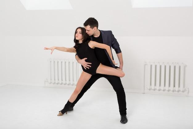 Beau couple dansant la bachata sur fond blanc en studio