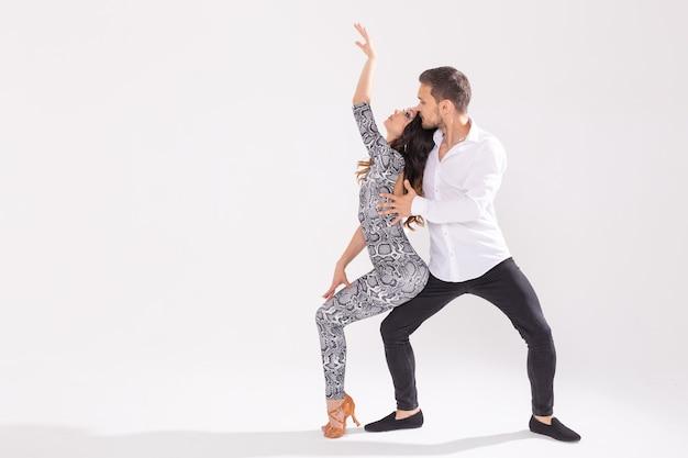Beau couple dansant la bachata sur un mur blanc avec espace copie