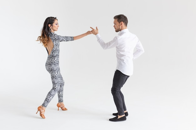 Beau couple danse bachata sur mur blanc