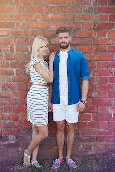 Beau couple debout devant le mur de briques