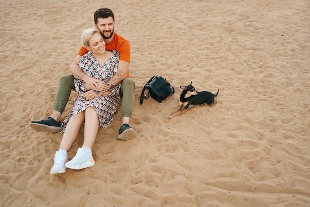 Beau couple de détente sur le sable étreignant et s'embrassant tout en jouant avec leur chien positif