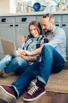 Beau couple de deux jeunes assis sur le sol de la cuisine et pointant vers un écran d'ordinateur portable