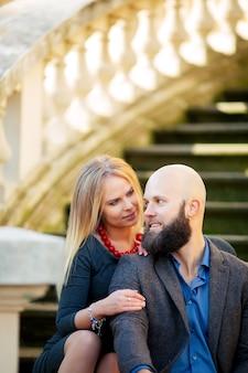 Un beau couple élégant de jeune femme et homme senior avec longue barbe noire assis embrassant près les uns des autres en plein air dans la rue d'automne dans les escaliers journée ensoleillée, photo horizontale