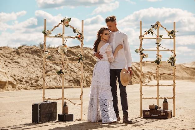 Beau couple élégant sur une plage de sable d'été, le concept du mariage dans le style boho