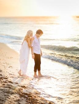 Beau couple élégant posant sur la plage