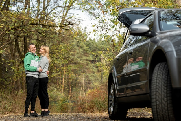 Beau couple embrassant derrière une voiture