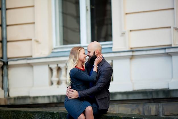 Un beau couple émotionnel élégant de jeune femme et homme senior avec une longue barbe noire embrassant assis près les uns des autres