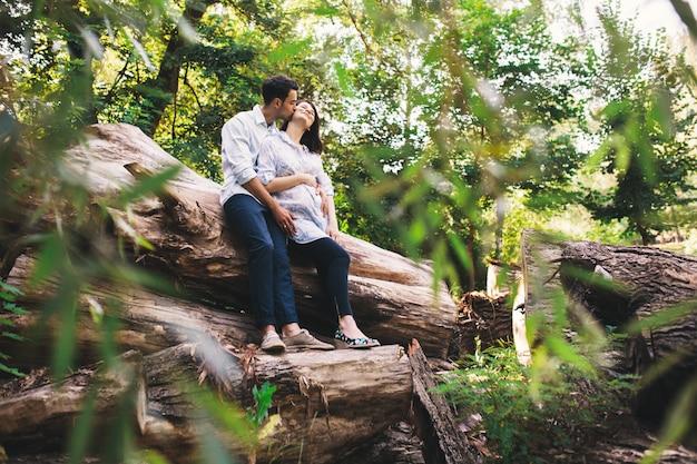 Beau couple enceinte se détendre à l'extérieur dans la forêt