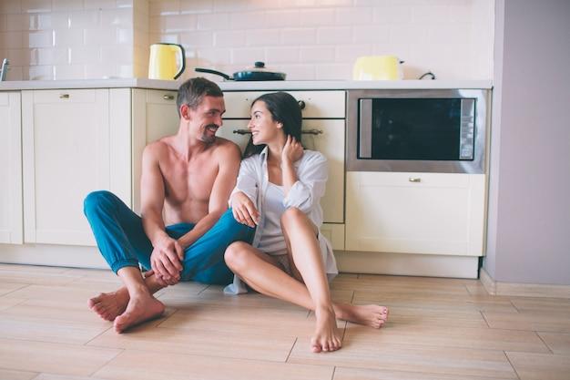Beau couple est assis sur le sol dans la cuisine et se regarde