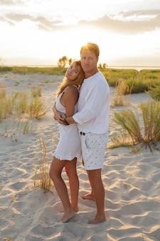 Beau couple européen embrassant contre le coucher du soleil sur la plage.