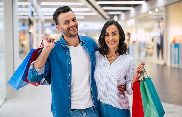 Beau couple excité heureux en amour ou en famille avec des sacs en papier dans les mains tout en marchant pendant les achats dans le centre commercial