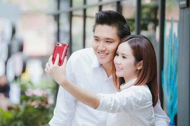 Beau couple faisant un selfie dans la ville