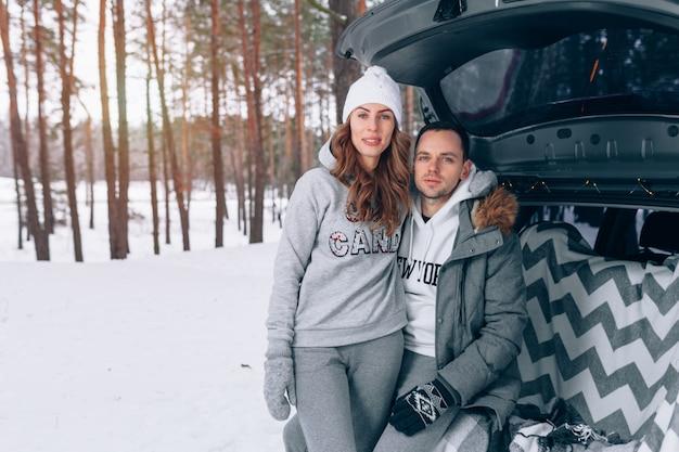 Beau couple familial dans une forêt enneigée assis dans le coffre de votre voiture