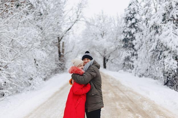 Un beau couple de famille marchant sur une route enneigée dans les bois