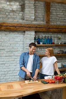Beau couple gai, cuisiner ensemble et s'amuser à la cuisine rustique