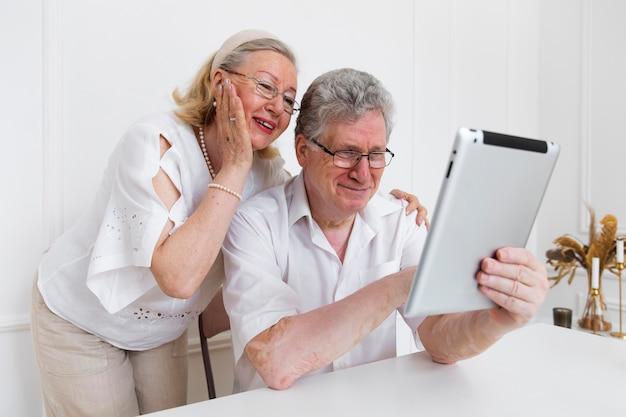 Beau Couple De Grands-parents Apprenant à Utiliser Un Appareil Numérique Photo gratuit