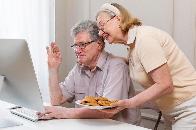 Beau couple de grands-parents apprenant à utiliser un appareil numérique