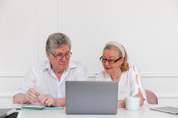 Beau couple de grands-parents apprenant à utiliser un ordinateur portable