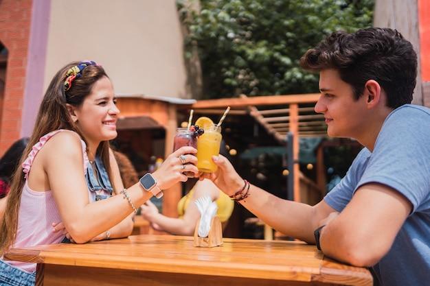 Beau couple grillage avec des jus de fruits.