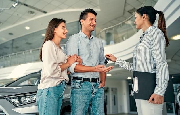 Un beau couple heureux a acheté une voiture chez le concessionnaire et reçoit les clés du gérant.
