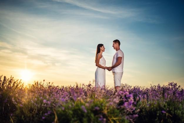 Beau couple heureux dans un champ de lavande. ambiance estivale fantastique, paysage floral de lever de soleil de fleurs de lavande des prés.