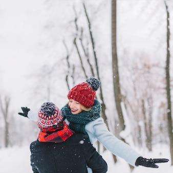 Beau couple heureux s'amuser dans les chutes de neige