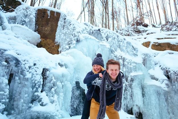Beau couple de hipster souriant debout sur un rocher, montagnes, cascade, sourire bienveillant deux gars en expédition d'aventure en montagne, paire à la mode d'amusement en plein air