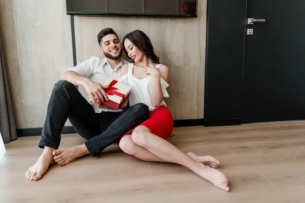 Beau couple homme et femme assis à la maison avec présent dans une boîte cadeau à la maison